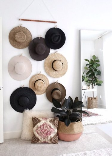 Hats hanging on wall, floor mirror, plants.