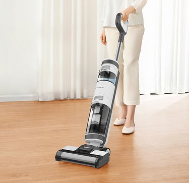 woman using white vacuum