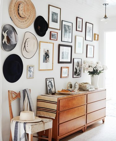 Farmhouse Chic Bedroom Ideas with Dresser with gallery wall, hats handing, chair.