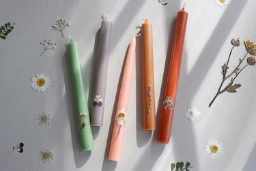 Five colorful DIY pressed floral taper candles on table surrounded with pressed flowers