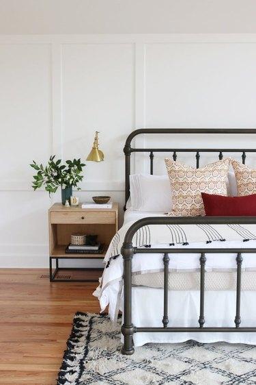 bedroom with metal bed, nightstand, plant, lamp, rug, pillows, hardwood floors