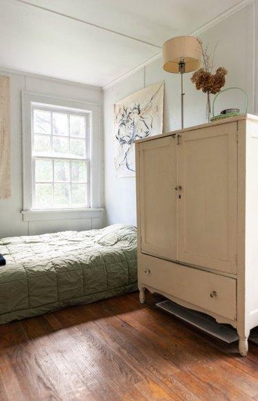 Armoire, bed, lamp, window, hardwood floors.