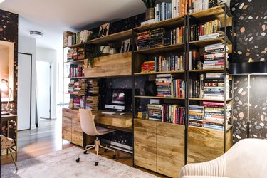 dark home office with a wall of industrial style bookshelves filled with books
