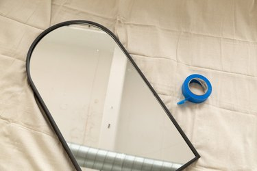 arched mirror and blue painter's tape