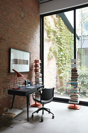 home office with brick wall, balck modern desk, and windows
