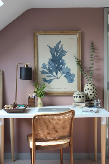 dark pink and purple walls in a home office with cane chair