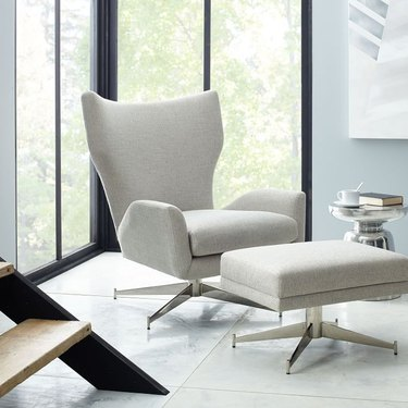 lounge chair and ottoman in light gray color near window
