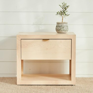 light wood nighstand with plant