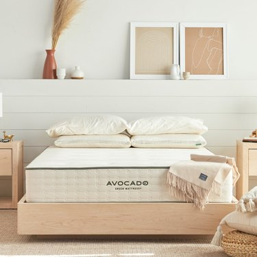 light wood bedframe with pillows and throw blanket