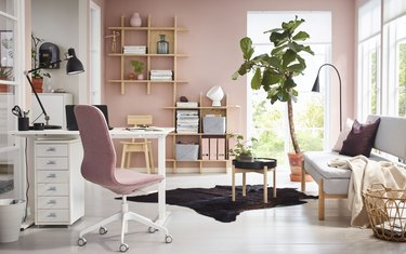 pink modern home office with plant and wall mounted shelves, sofa, and folding desk