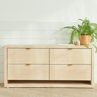 light wood four-drawer dresser with plant