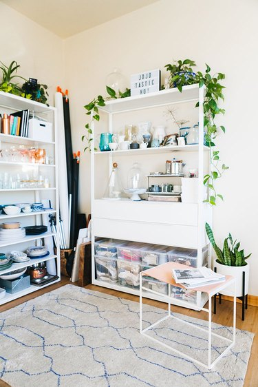 white home office with white open bookshelves with plants on the top shelf