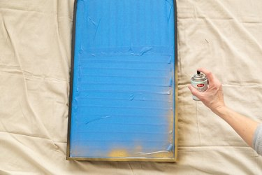 spray painting a mirror frame in gold