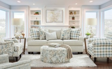 living room with couch, chairs, ottoman, lamps, rug in plaid and floral patterns