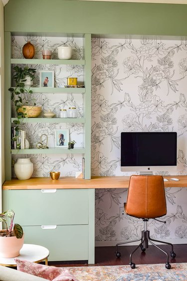 green home office built-ins with a black and white wallpapered backdrop, leather desk chair