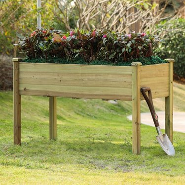 An elevated wooden planter with a shovel leaning against it
