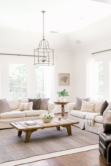 Farmhouse living room with two couches, pillows, chandelier, coffee table, rug.
