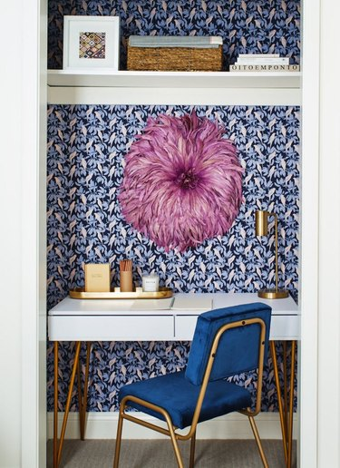 closet home office with blue parrot print wallpaper, blue velvet desk chair and large pink, feathered wall hanging