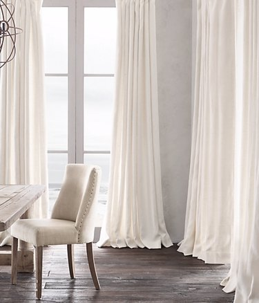 White linen curtains, wood floor, chair, table.
