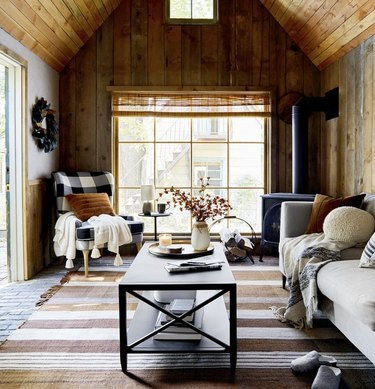 Cabin living room with couch, plaid chair, coffee table, pillows, throws, wood panel walls.