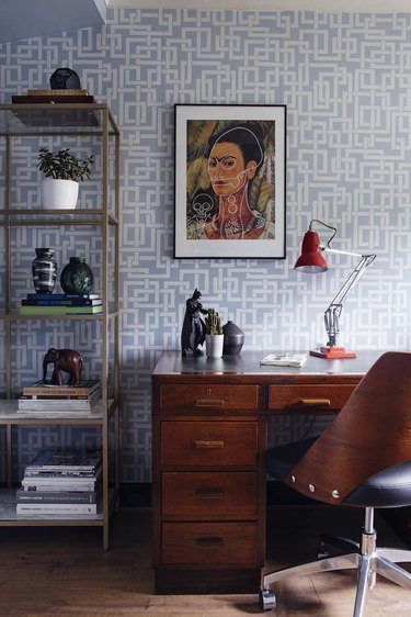 mid century modern home office with farrow and ball enigma wallpaper in blue, portrait of frida khalo hanging above the desk