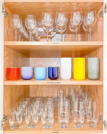cabinet with organized stemware, colorful and clear glasses