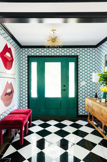 Hallway Pendant Light in Maximalist hallway with black and white floors, wallpaper, art, benches, gold light, credenza, green door.