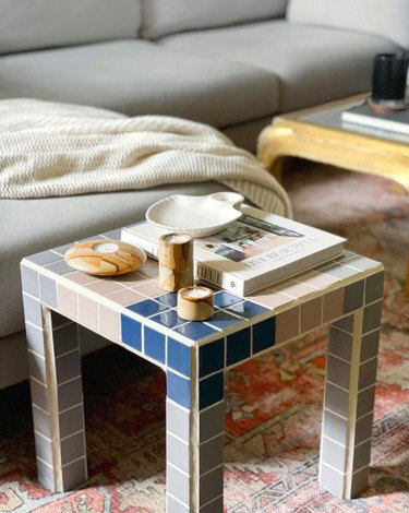 tiled coffee table near gray couch