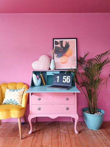 hot pink maximalist home office with pink secretary desk and yellow accent chair