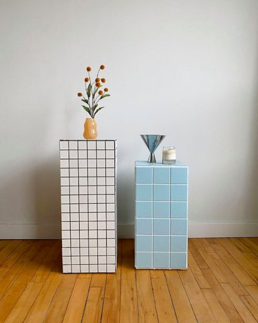 two tiled side tables with flowers and other items on top