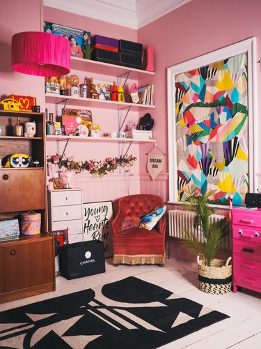 pink maximalist home office with large bookcase and vibrant wall art, red lounge chair in the corner