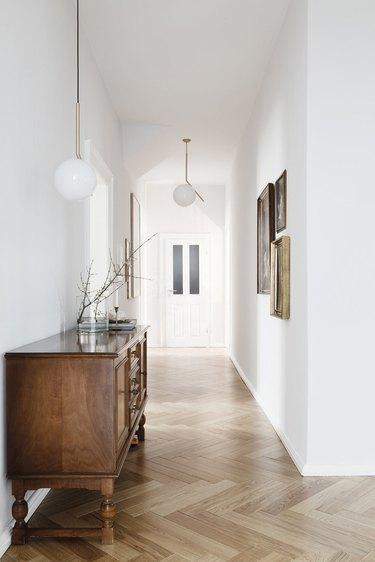 Hallway Pendant Light in Hallway with credenza, wood floors, globe pendant lamps, art.