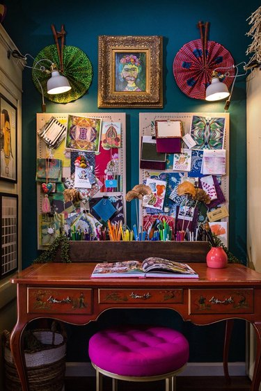 blue maximalist home office with large mood board hanging above the desk