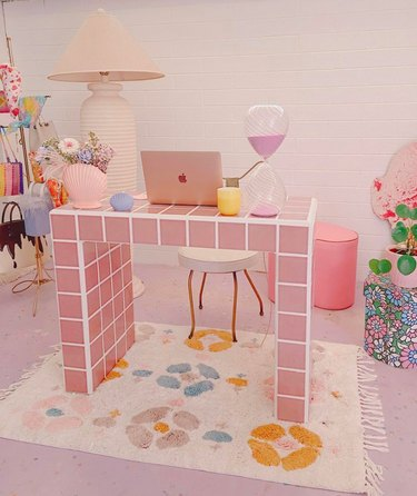 pink tile desk in space with laptop and lamp and floral rug underneath