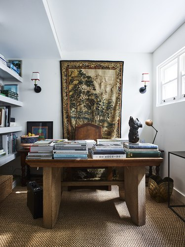 white maximalist home office with earthy accents, a wooden desk and tapestry hanging behind the desk