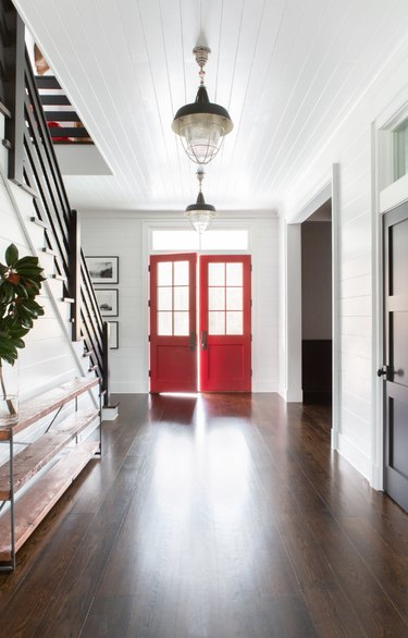 Hallway Pendant Light in Entryway with red doors, pendant lights, wood floors, stairs, credenza.