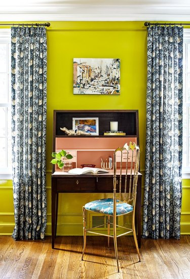 chartreuse maximalist home office with blue patterned curtains and wooden secretary desk