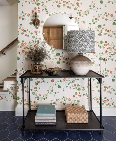 Entryway with floral wallpaper, console table, lamp, books, mirror.