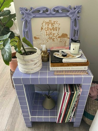 purple tiled table with plant, books, and records
