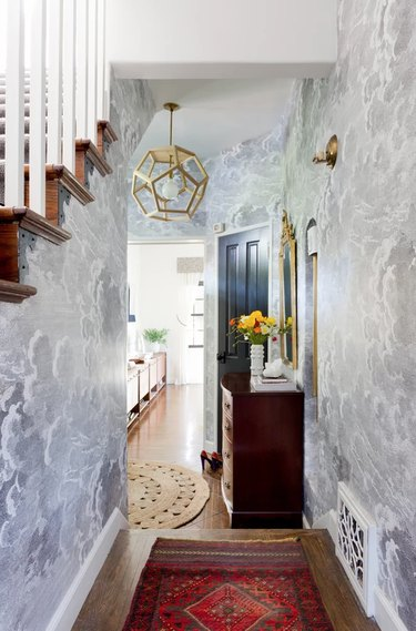 Hallway Pendant Light in Entryway with wallpaper, rug, pendant light, stairs.