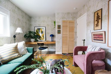 subdued maximalist home office with leafy wallpaper, pink sofa, green sofa and plants