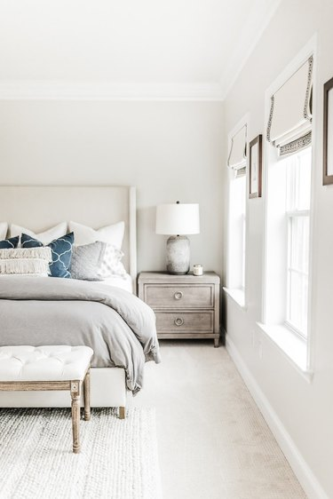 gray cement lamp on top of washed wooden dresser in guest bedroom