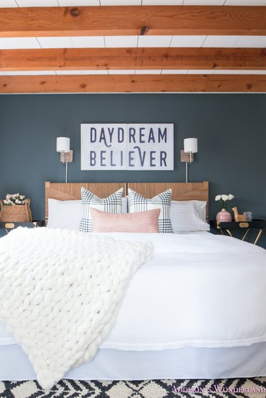 small wall lights above rattan headboard in modern farmhouse bedroom