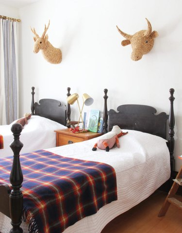 twin kids bedroom with brass table lamp and rattan animal heads