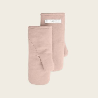 two pale pink oven mitts