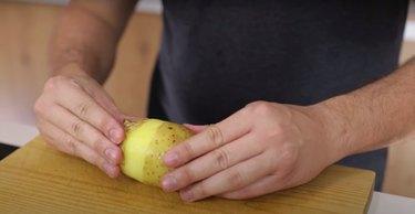 person peeling skin off of potato on wood cutting board