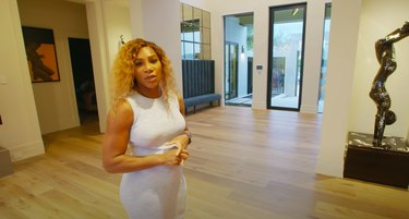 Serena Williams standing in home with sculpture nearby