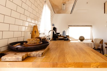 wood countertop in kitchen with white subway tile backsplash