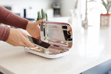 hand putting phone into phone sanitizer on counter