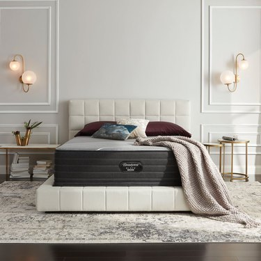 beautyrest mattress on white tufted bedframe with a blanket and pillows